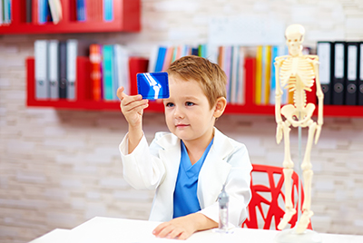 cute kid playing a doctor, looking at x-ray image of leg