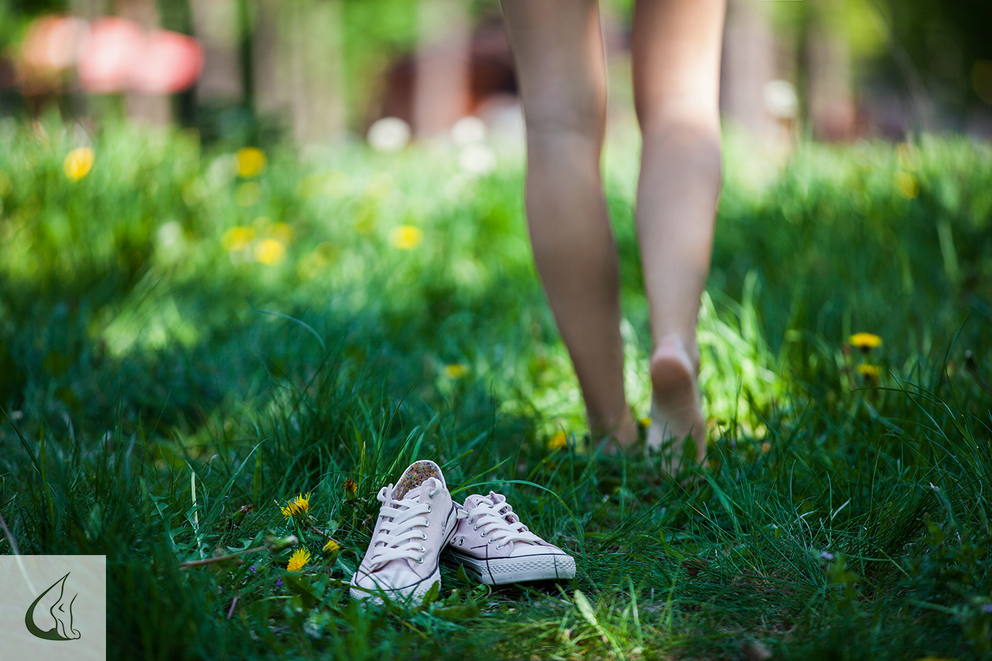 Woman walking barefoot on the grass, pink shoes in focus, shallo